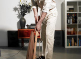 Man using vacuum cleaner to clean floor   Original Filename: 82133035.jpg